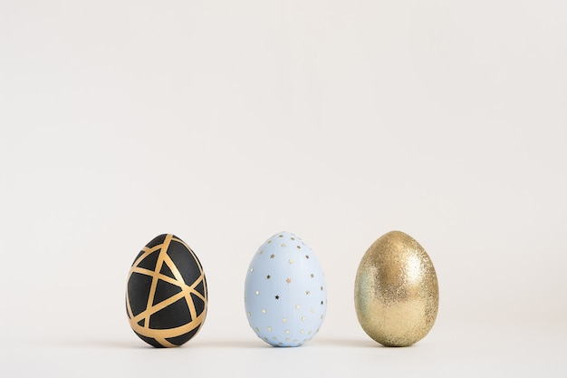 Tre uova decorate dorate di pasqua su superficie blu. minimo concetto di pasqua.