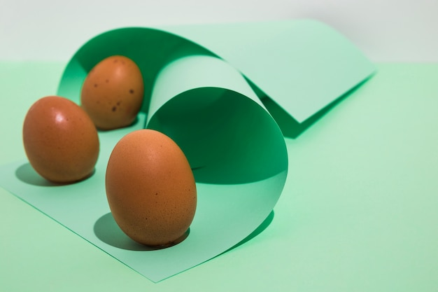 Tre uova di gallina marrone con carta arrotolata sul tavolo