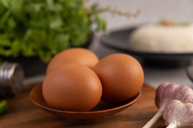 Tre uova di gallina sul piatto con aglio.