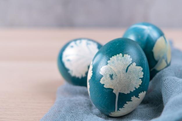 Tre uova di pasqua blu organico in piedi sul tavolo di legno