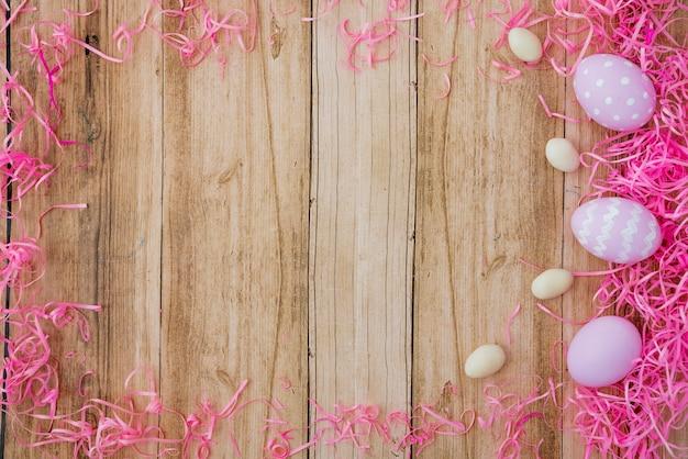 Tre uova di pasqua colorate sul tavolo di legno