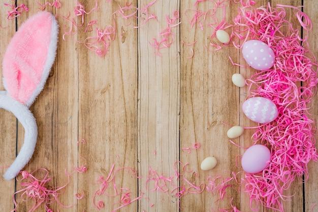 Tre uova di pasqua con orecchie da coniglio sul tavolo