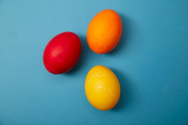 Tre uova di pasqua su sfondo blu