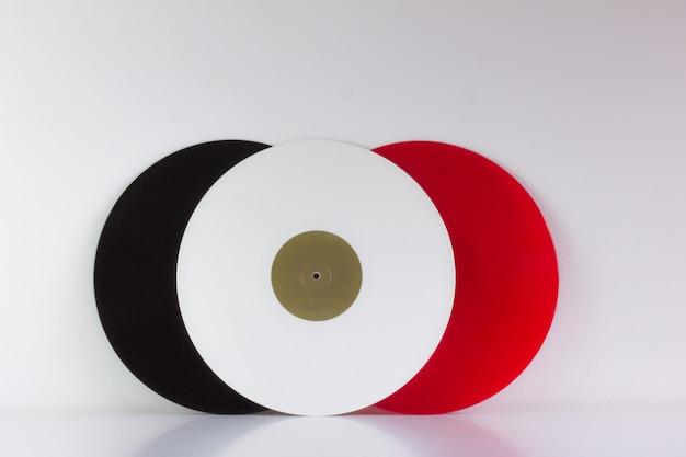 Tre vinili, neri, rossi e bianchi, su bianco, con spazi bianchi