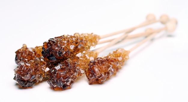 Tre zucchero candito su un bastone su sfondo bianco