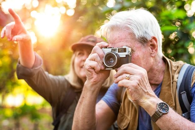 Trekker senior che prende una foto con una macchina da presa