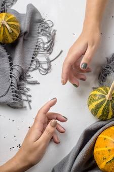 Trend manicure in colori autunnali su un tavolo grigio accanto a zucche e una sciarpa grigia