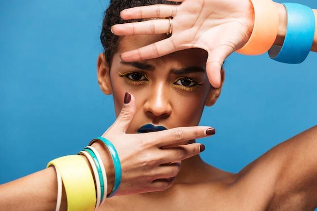 Trendy ritratto di donna mulatta spaventata o elettrizzata con trucco alla moda e accessori che copre il viso con le mani, oltre il muro blu