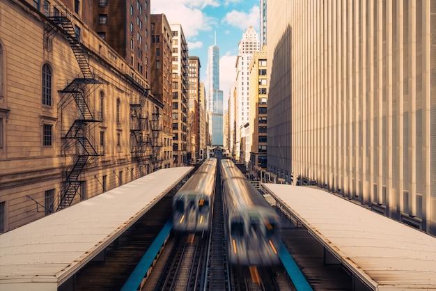 Treni che arrivano alla stazione ferroviaria tra edifici nel centro di chicago, illinois.
