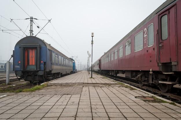 Treni in attesa in una stazione ferroviaria. una giornata nebbiosa