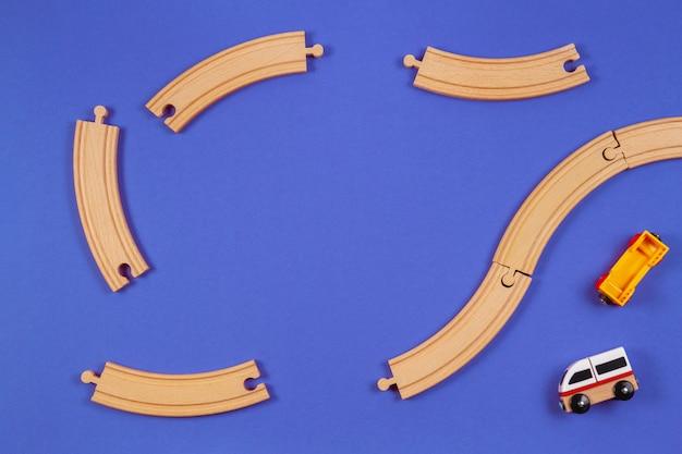 Trenino in legno e pezzi di rotaie in legno su sfondo di colore blu