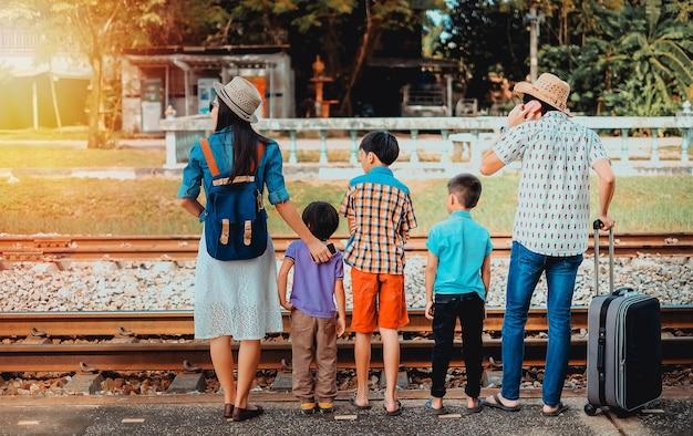 Treno aspettante del viaggiatore della famiglia dell'asia che viene in vacanza