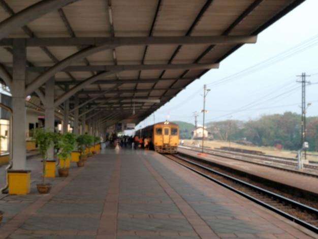 Treno offuscata con stazione ferroviaria