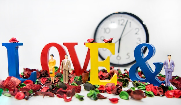 Triangolo amoroso. foto astratta di amore e amanti. grandi lettere di legno con piccole figure di plastica.