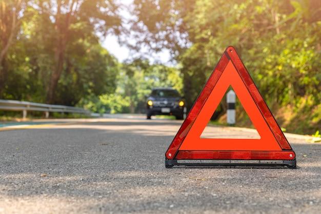Triangolo rosso, segnale di arresto di emergenza rosso, simbolo di emergenza rosso e fermata dell'auto nera e parcheggio sulla strada.