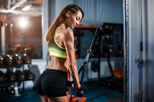 Tricipiti adatti di allenamento della donna che sollevano i pesi in palestra