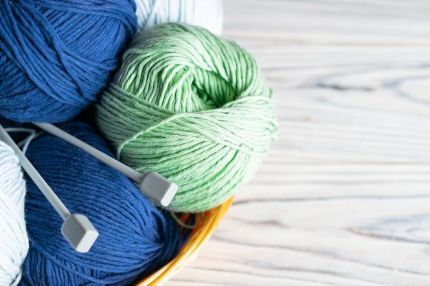 Tricottando la composizione in hobby con filato e gli aghi blu e verdi su di legno bianco