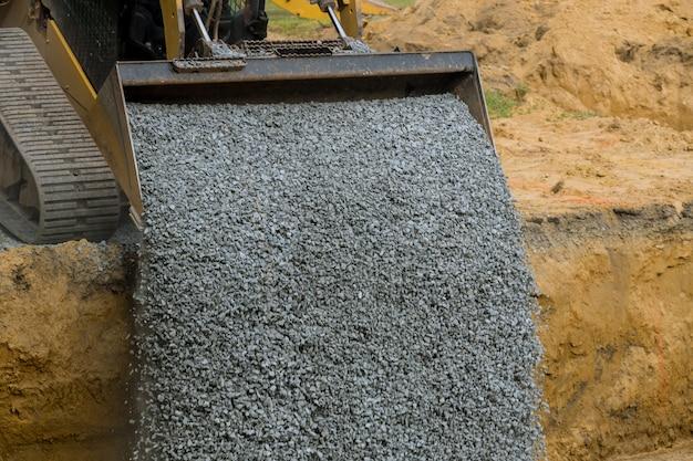 Trincea di riempimento della benna dell'escavatore per il riempimento di pietra della fondazione