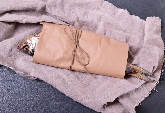 Triotto di pesce essiccato avvolto in carta marrone artigianale