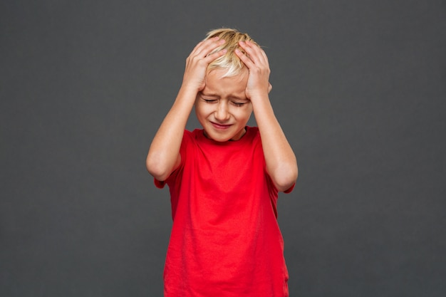 Triste bambino ragazzo con mal di testa