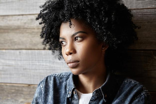 Triste bella donna dalla pelle scura che indossa camicia di jeans guardando lontano con espressione seria sul viso sentirsi infelice