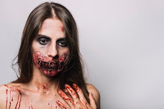 Triste donna con la faccia danneggiata toccando la spalla
