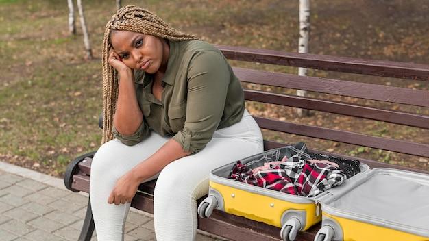 Triste donna seduta accanto al suo bagaglio aperto con copia spazio