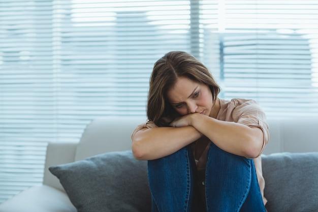 Triste donna seduta sul divano
