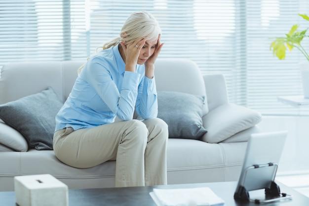 Triste donna senior sul divano