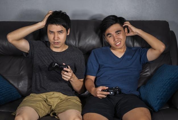 Triste due uomini che giocano ai videogiochi e perde