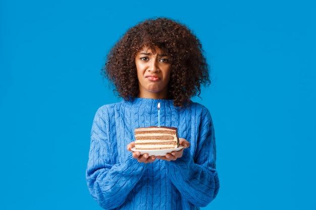 Triste e cupa, depressa ragazza afro-americana sentirsi sola per il suo compleanno, nessuno è venuto a una festa, con in mano una torta con una candela accesa, imbronciata e in piedi sul muro blu