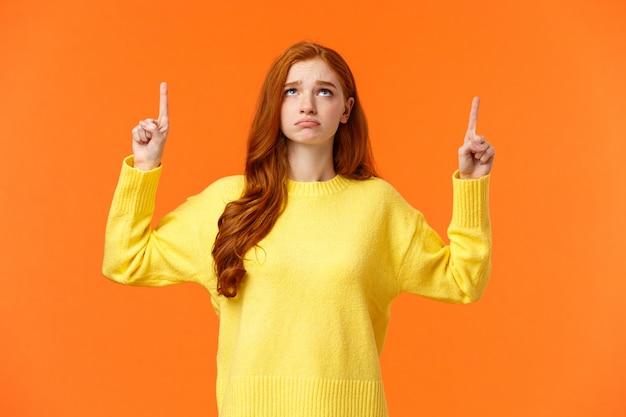 Triste e infelice donna rossa imbronciata in maglione giallo, insoddisfatto, sembra cupo durante le vacanze di natale