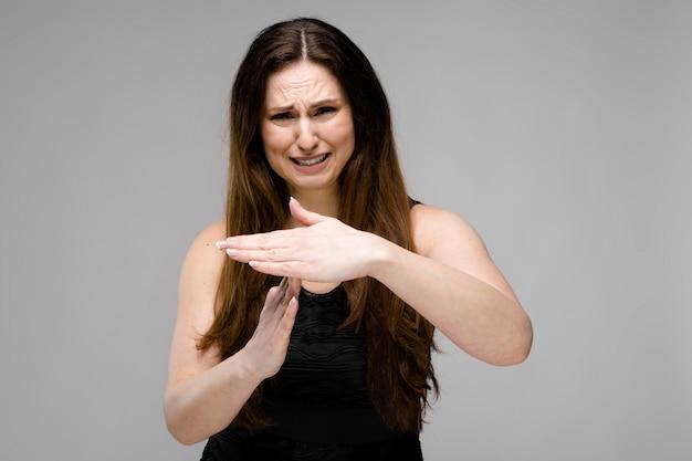 Triste emotivo plus size modello in piedi in studio mostrando stop gesto mostra time-out segno