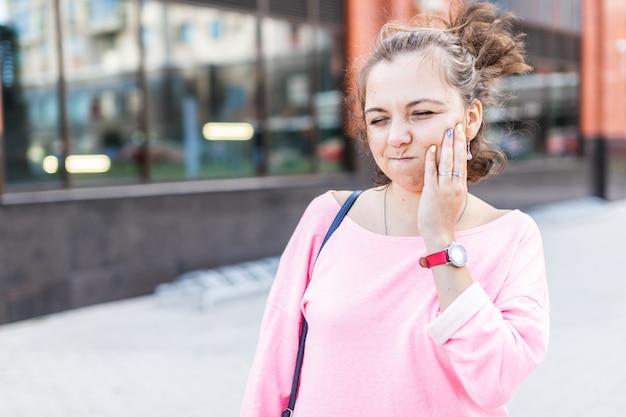 Triste giovane donna che soffre di mal di denti grave mentre si cammina sulla strada estiva.