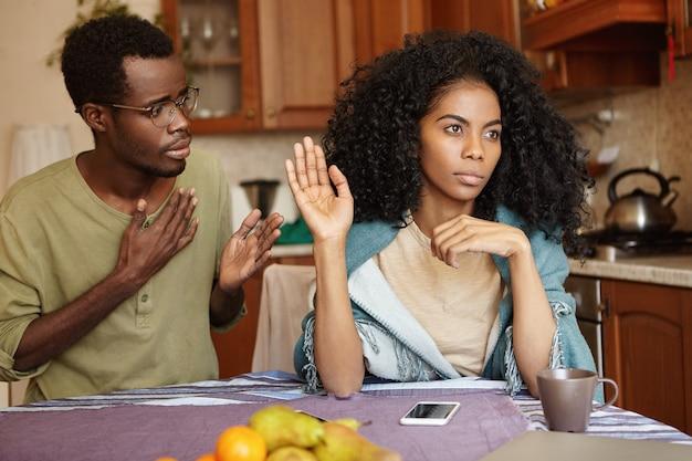 Triste maschio afro-americano in bicchieri tenendo la mano sul petto, scusandosi con la moglie arrabbiata e pazza