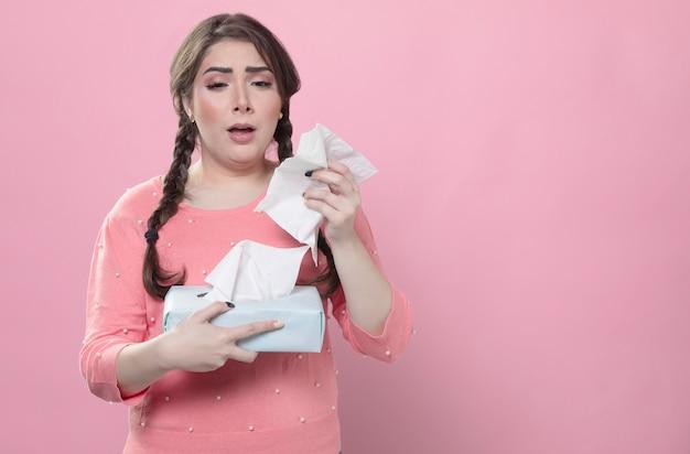 Triste per starnutire mentre tiene i tovaglioli