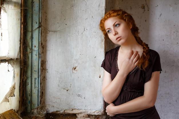 Triste ragazza dai capelli rossi in piedi vicino a una finestra rotta, il concetto di povertà e miseria