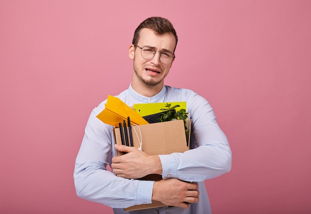 Triste ragazzo piuttosto piangente con una scatola di cartone con penne, aeroplanino di carta e cose diverse