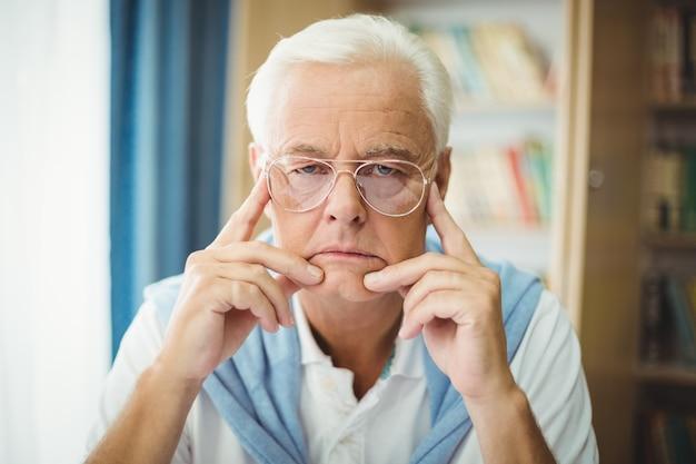 Triste uomo anziano seduto al tavolo