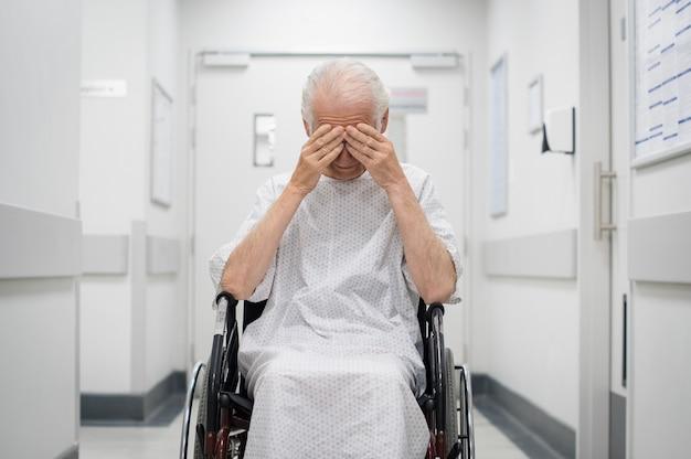 Triste uomo anziano su sedia a rotelle