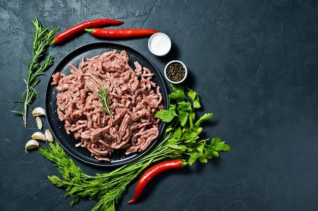 Tritato crudo su un piatto nero. ingredienti per cucinare, rosmarino, peperoncino, aglio, sale, prezzemolo, aneto.