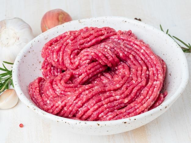Triti il manzo, carne macinata con gli ingredienti per la cottura sulla tavola rustica di legno bianca, vista laterale