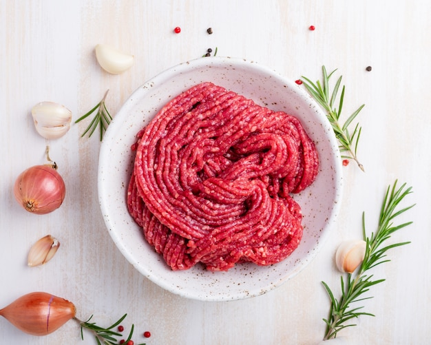 Triti il manzo, carne macinata con gli ingredienti per la cottura sulla tavola rustica di legno bianca
