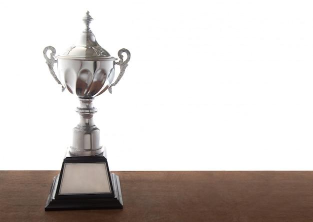 Trofeo d'argento sulla tavola di legno isolato su sfondo bianco. premi vincenti