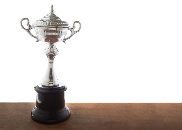 Trofeo d'argento sulla tavola di legno isolato su sfondo bianco.