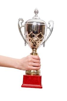 Trofeo della tazza della holding della mano isolato su bianco