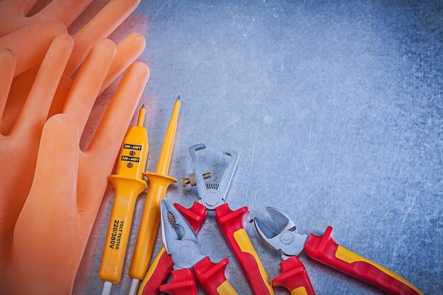 Tronchesi elettriche delle pinze del tester del tester dei guanti isolate filo dei guanti di gomma sulla tavola metallica