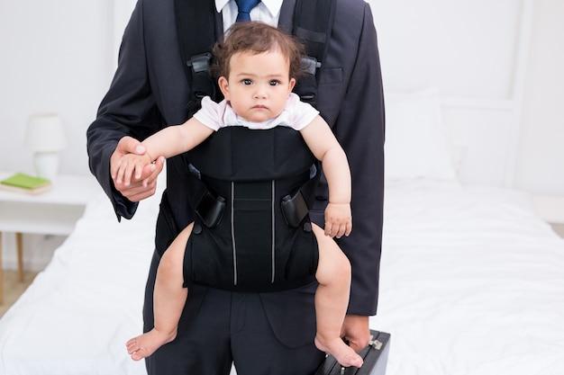 Tronco del padre che trasporta bambino e valigetta