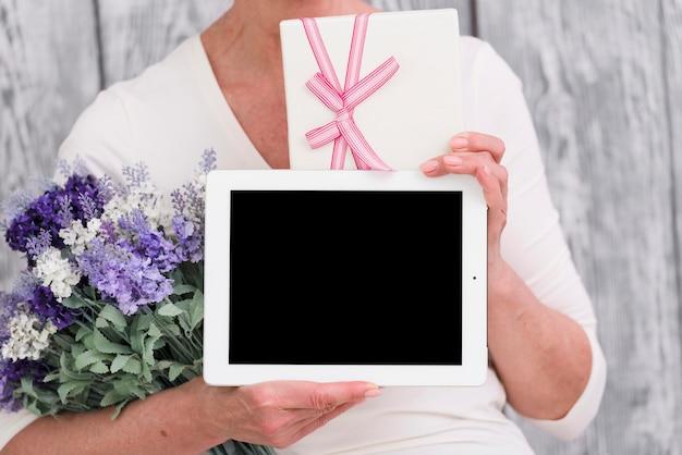 Tronco di una donna con scatola regalo; bouquet di fiori e tavoletta digitale schermo vuoto in mano