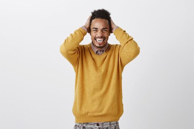 Troppo dolore per una testa. ritratto di dispiaciuto scomodo attraente afroamericano in maglione giallo che tiene le mani sui capelli, smorfie e strabismo, sensazione di disagio e mal di testa